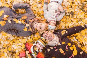 High angle view of happy parents having fun with their children during autumn. They are lying down in heap of leaves and looking at camera.
